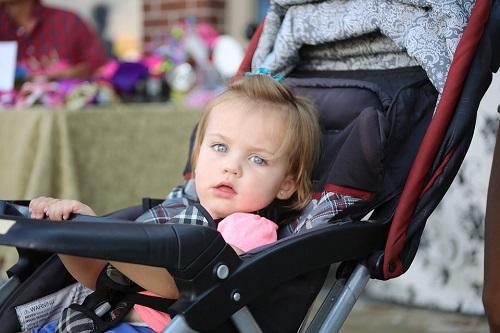 Girl in stroller waring pink shirt